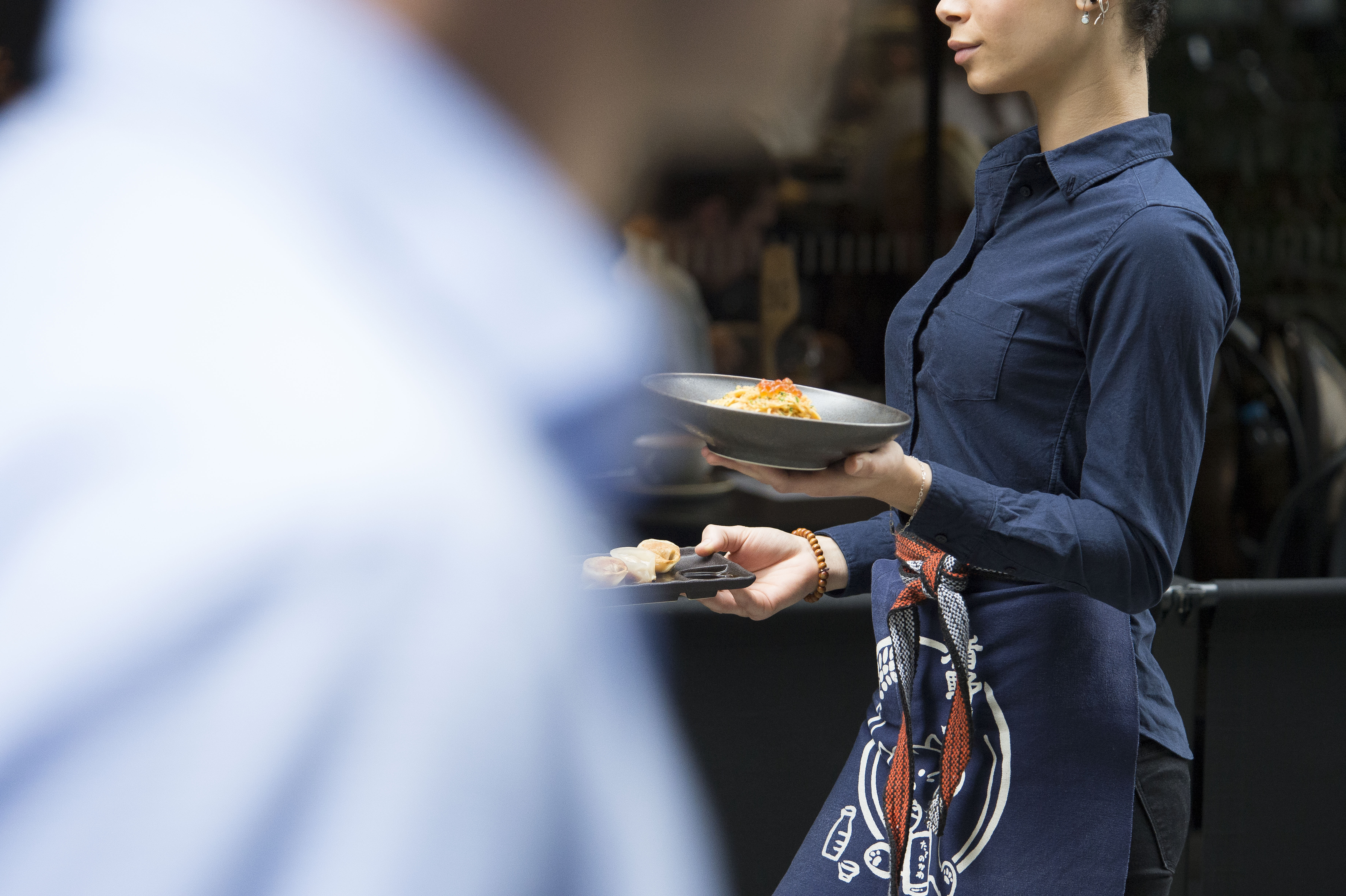 waitress bringing a plate of food to customers